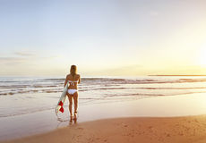 Giovane bella ragazza del surfista che cammina verso la spuma all'alba Fotografie Stock