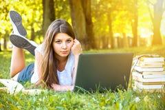 Giovane bella ragazza dello studente di college che per mezzo del computer portatile Fotografie Stock Libere da Diritti