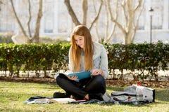 Giovane bella ragazza dello studente sull'erba del parco della città universitaria con i libri che studia esame preparante felice Fotografia Stock