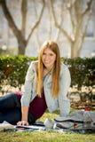 Giovane bella ragazza dello studente sull'erba del parco della città universitaria con i libri che studia esame preparante felice Fotografie Stock Libere da Diritti