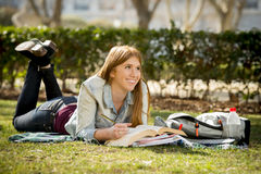 Giovane bella ragazza dello studente sull'erba del parco della città universitaria con i libri che studia esame preparante felice Fotografia Stock Libera da Diritti