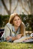 Giovane bella ragazza dello studente sull'erba del parco della città universitaria con i libri che studia esame preparante felice Immagini Stock