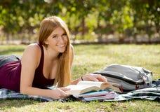Giovane bella ragazza dello studente sull'erba del parco della città universitaria con i libri che studia esame preparante felice Fotografie Stock