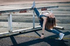 Giovane bella ragazza di sport dei capelli biondi che fa allungando esercizio Immagini Stock
