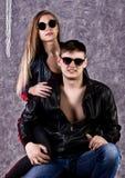 Giovane bella ragazza e tipo bello in bomber ed occhiali da sole che posano su un seggiolone e che baciano sul gray fotografia stock