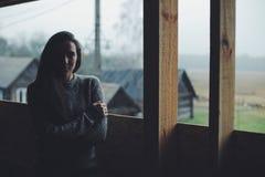 Giovane bella ragazza nel villaggio Modello su fondo di una casa di legno nel villaggio Indicatore luminoso scuro fotografia stock