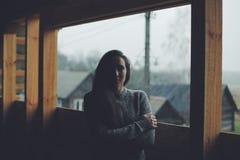 Giovane bella ragazza nel villaggio Modello su fondo di una casa di legno nel villaggio Indicatore luminoso scuro immagine stock libera da diritti