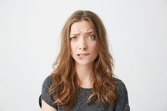 Giovane bella ragazza nervosa che esamina il labbro mordace aggrottante le sopracciglia della macchina fotografica sopra fondo bi Fotografia Stock