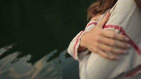 Giovane bella ragazza pagana dello slavo che sta vicino al lago in montagne carpatiche archivi video