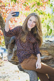 Giovane bella ragazza sorridente che fa selfie in parco Fotografie Stock