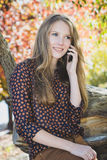 Giovane bella ragazza sorridente che parla sul telefono cellulare in parco Immagine Stock Libera da Diritti