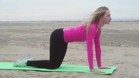 Giovane bella ragazza sportiva che fa gli esercizi sulla sabbia Gambe d'allungamento relative alla ginnastica archivi video