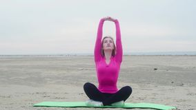 Giovane bella ragazza sportiva che fa gli esercizi sulla spiaggia Allungamento relativo alla ginnastica stock footage