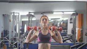 Giovane bella ragazza sportiva che fa la stampa della spalla con le teste di legno che si esercita in una palestra di sport archivi video