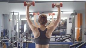 Giovane bella ragazza sportiva che fa la stampa della spalla con le teste di legno che si esercita in una palestra di sport, vist video d archivio