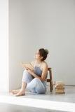 Giovane bella ragazza tenera che sorride esaminando il libro della tenuta della finestra che si siede sul pavimento sopra la pare Immagini Stock Libere da Diritti