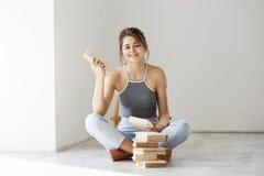 Giovane bella ragazza tenera che sorride esaminando il libro della tenuta della macchina fotografica che si siede sul pavimento s Immagine Stock