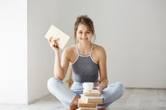 Giovane bella ragazza tenera che sorride esaminando il libro della tenuta della macchina fotografica che si siede sul pavimento s Immagine Stock Libera da Diritti