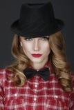 Giovane bella ragazza in un cappello ed in una camicia rossa fotografie stock libere da diritti