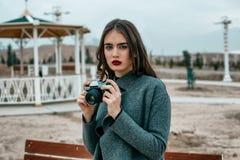 Giovane bella ragazza in un cappotto grigio con le pose d'annata della macchina fotografica nella sera fotografia stock