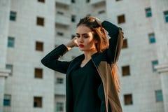 Giovane bella ragazza in un rivestimento nero che posa contro il contesto di alta casa bianca fotografia stock