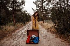 Giovane bella ragazza in un vestito d'annata giallo che posa su una strada campestre fangosa con una retro valigia aperta in sue  fotografia stock libera da diritti