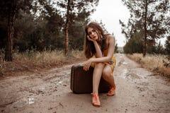 Giovane bella ragazza in un vestito d'annata giallo che posa su una strada campestre fangosa, sedentesi su una retro valigia immagini stock