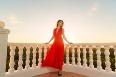 Giovane bella ragazza in un vestito rosso che sta accanto alla pietra g Immagini Stock