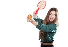 Giovane bella ragazza in una blusa verde che tiene una mela con sorridere della racchetta di tennis Apple vuole colpire la racche Fotografia Stock Libera da Diritti