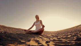 Giovane bella ragazza in vestiti bianchi che fanno yoga archivi video