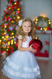 Giovane bella ragazza in vestito da sera elegante bianco blu che si siede sul pavimento vicino all'albero di Natale e sui present Fotografie Stock Libere da Diritti