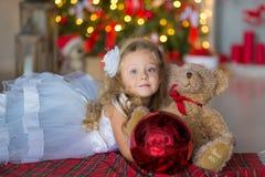 Giovane bella ragazza in vestito da sera elegante bianco blu che si siede sul pavimento vicino all'albero di Natale e sui present Fotografie Stock