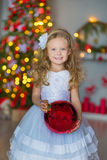 Giovane bella ragazza in vestito da sera elegante bianco blu che si siede sul pavimento vicino all'albero di Natale e sui present Fotografia Stock Libera da Diritti