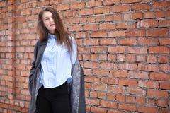 Giovane bella ragazza vicino alla posa rossa del muro di mattoni Fotografia Stock