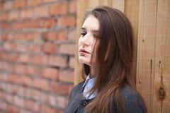 Giovane bella ragazza vicino alla posa rossa del muro di mattoni fotografia stock libera da diritti