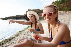 Giovane bella risata delle ragazze, indicando le dita via, trovantesi vicino al mare Fotografia Stock Libera da Diritti