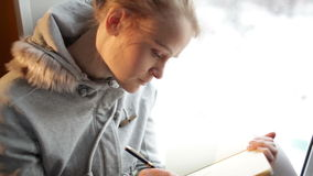 Giovane bella scrittura della ragazza nel suoi giornale e fantasticare. stock footage