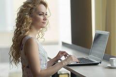 Giovane bella seduta femminile con il taccuino portatile in caffetteria durante il tempo di ricreazione Fotografia Stock Libera da Diritti