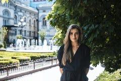 Giovane bella signora alla moda che sta all'ombra di grande verde Fotografie Stock Libere da Diritti