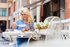 Giovane bella signora con il messaggio luminoso stupefacente della lettera della lettura di sorriso mentre sedendosi nella barra  Fotografie Stock Libere da Diritti