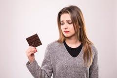 Giovane bella signora felice che mangia cioccolato e sorridere Ragazza che assaggia cioccolato zuccherato La giovane donna con na immagini stock libere da diritti