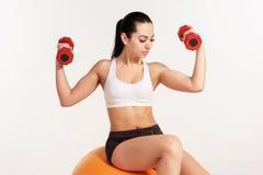 Giovane bella sportiva con le teste di legno che si esercita sul fitball Fotografia Stock