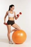 Giovane bella sportiva con le teste di legno che si esercita sul fitball Fotografia Stock Libera da Diritti