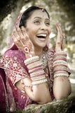 Giovane bella sposa indù indiana che ride sotto l'albero con le mani dipinte sollevate Immagini Stock