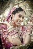 Giovane bella sposa indù indiana che ride sotto l'albero con le mani dipinte sollevate Fotografia Stock