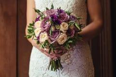 Giovane bella sposa nel mazzo bianco di nozze della tenuta del vestito, mazzo della sposa da spruzzo crema rosa, cespuglio di ros Immagini Stock