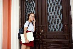 Giovane bella studentessa sorpresa in vetri che stanno porta vicina, eavesdroping Immagini Stock Libere da Diritti