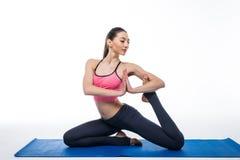 Giovane bella yoga della donna che posa sul fondo bianco isolato dello studio Fotografie Stock