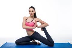 Giovane bella yoga della donna che posa sul fondo bianco isolato dello studio Fotografia Stock