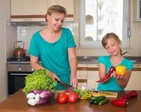Giovane belle donna e ragazza che producono l'insalata della verdura fresca Concetto interno sano dell'alimento Madre sorridente  Fotografie Stock